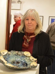 Potter Cathy Cramer is pictured with one of her pottery