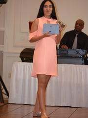 Desiree Fonseca of Millville models a designer clutch