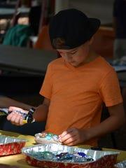 Carter Siniavsky, 9, of Vineland makes a mosaic rock