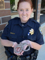 Lauren Reid, police officer with the University of Nevada, Reno Police Department, holds the handcuffs of former Reno police Officer John Bohach, killed 13 years ago today in a gun fight.