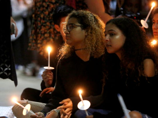 Broward County students Yanelle Ayala, left, and Brianna Heiges, both 17, mourn their community's loss during a candlelight vigil for the victims of last week's shooting at Marjory Stoneman Douglas High School held Monday at the Centre of Tallahassee.