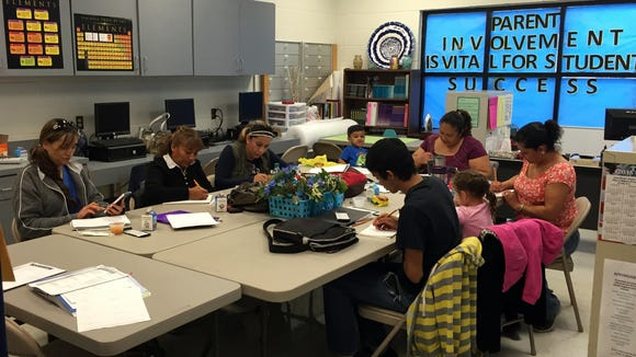 Parents prepare to take the General Education Development test during an class in Anthony High School's parent center on Oct. 28.