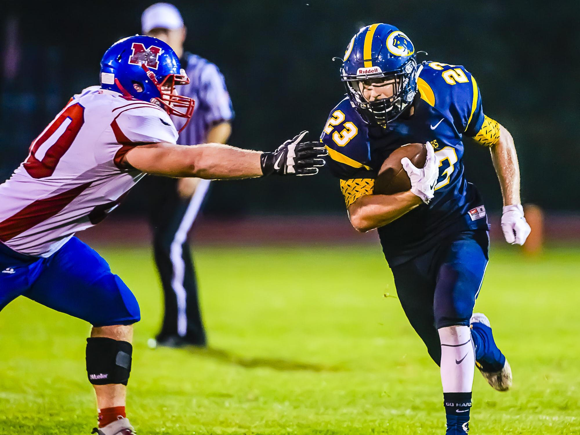 JD Ross, right, of DeWitt runs past a Mason defender for a first down late in the second quarter of their game Sept. 18 in DeWitt.
