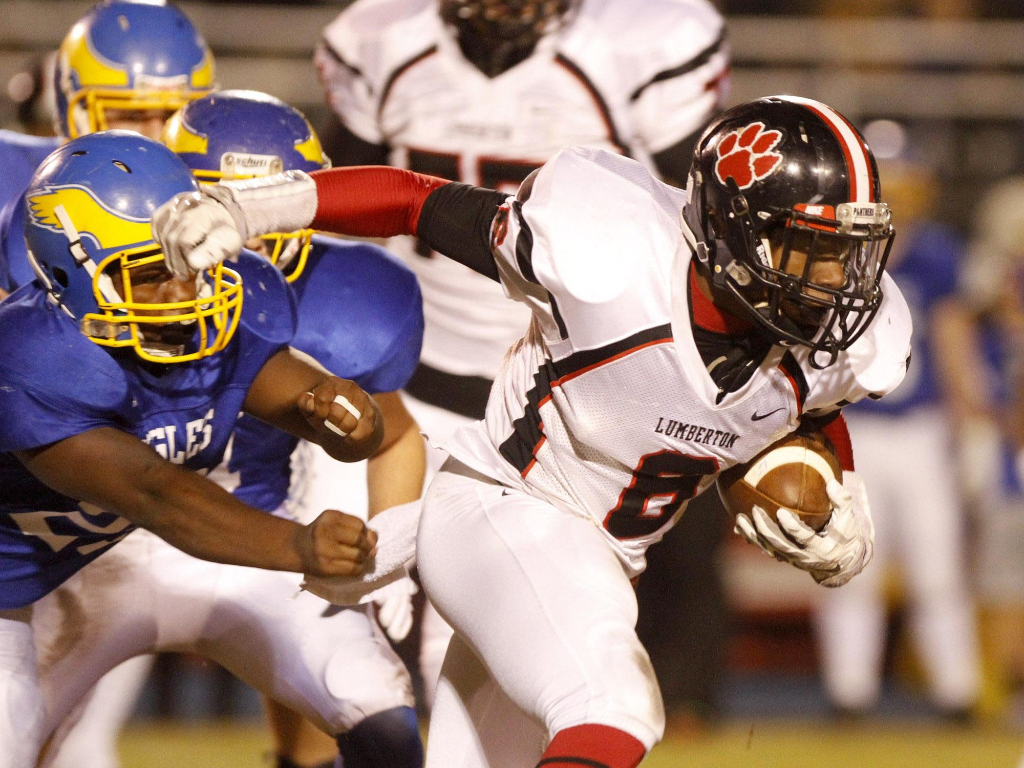 Lumberton running back Daylon Burks runs out of the grasp of Resurrection's Cearly Parker IV, Friday night in the Class 1A South State Championship.