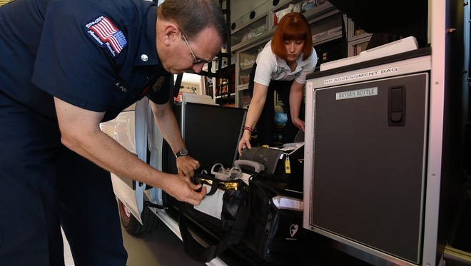 Paramedic Scott Fox and nurse practitioner Victoria Morrison check equipment in the ambulance they respond to 911 calls in.