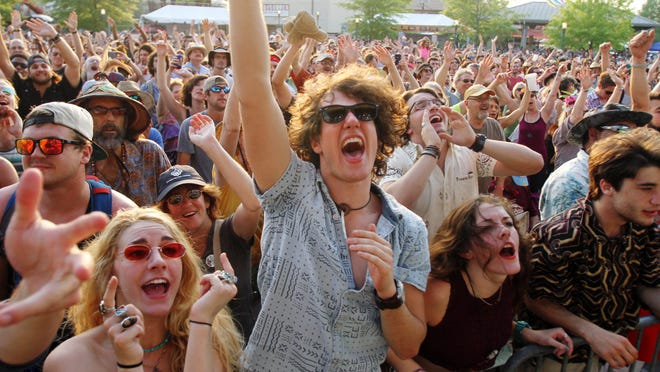 From left, Gabrielle Giosa, Lynden Segura and Dominique Giosa cheer as they and thousands of other Festival-goers listen to the Funky Meters during Festival International de Louisiane Sunday .