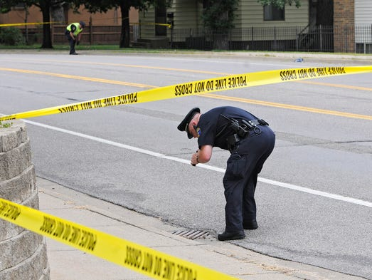A St. Cloud Police officer searches for evidence on Ninth Avenue South near the intersection of 12th Street South in St. Cloud Saturday.