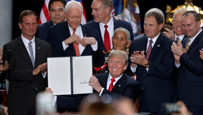 President Donald Trump holds up a signed proclamation to shrink the size of Bears Ears and Grand Staircase Escalante national monuments at the Utah State Capitol Monday, Dec. 4, 2017, in Salt Lake City.