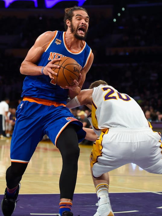 New York Knicks center Joakim Noah, left, gets by Los Angeles Lakers center Timofey Mozgov (20), of Russia, as he drives to the basket during the first half of an NBA basketball game Sunday, Dec. 11, 2016, in Los Angeles.(AP Photo/Gus Ruelas)
