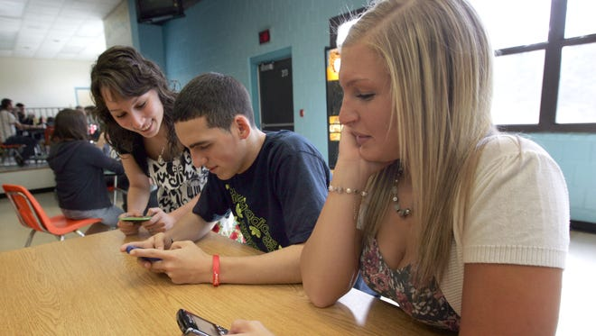 Pinelands Regional High School is among those that changed their policies on cellphone use. From left, Ozgul Yilmaz, John Roman and Katherine Bezak send text messages during lunch. Tim McCarthy/Staff Photographer Little Egg Harbor Twp.  03/08/12 - Pinelands Regional High Scool - Social Media and Cell phone use in schools. Pinelands schools changed their policy on cell phone use. Ozgul Yilmaz, John Roman and Katherine Bezak all 18 and from Little egg send messages during lunch.  Tim McCarthy/Staff Photographer