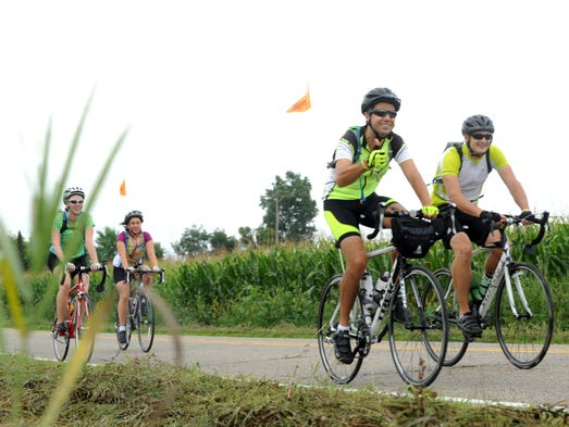 Bicyclists ride past the cornfields on DeWitt Road as DALMAC riders began their journey Wednesday morning after leaving East Lansing.