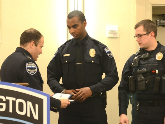 Burlington police Chief Brandon del Pozo, left,  presents