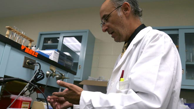 Tony Tambasco, the director for the Mansfield Police Crime Lab, demonstrates in his lab of how drug samples are tested.
