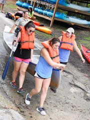 Koreshan Park Specialist Brittany Petit helps FGCU student volunteers Alexis Soros, Lindsey Lewis and Summer Adams launch their canoe for a cleanup of the Estero River Sept. 24 as part of National Public Lands Day.