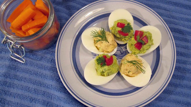 Eggs are stuffed with tuna, topped with dill and guacamole and topped with tomatoes.