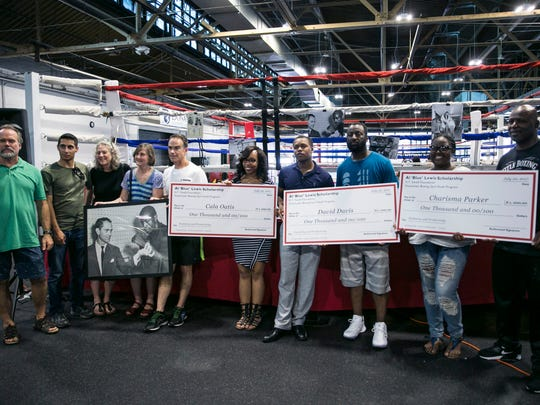 Scholarship recipients received their checks at a the Downtown Boxing Gym during a reception on Thurs., July 20, 2017.