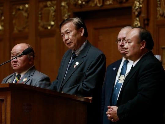 Gen. Vang Pao's son Vang Chong Vang, middle, gives