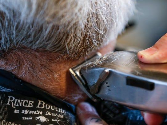 Chad Dunivent trims up Scott Roussel's beard as he