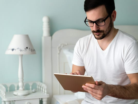 Young man reading news before bed