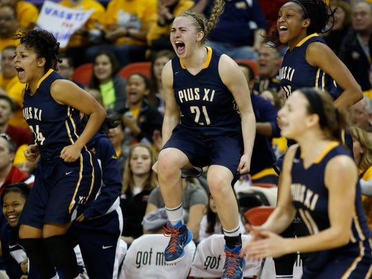 Pius XI's Gabby Green, left, Olivia Freckmann, center, and Vashti Nwagbaraocha, right, jump from the bench in celebration during their game against Waunakee in the Division 2 semifinals.