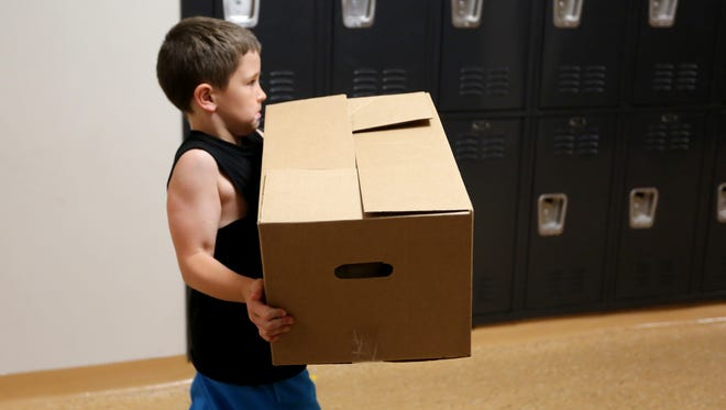 Hunter Thompson, 8, helps deliver Power Packs from the Freestore Feedbank to students at Oyler School in Lower Price Hill. During the school year, the packs go to 175-200 students on Fridays to feed the kids over the weekend.