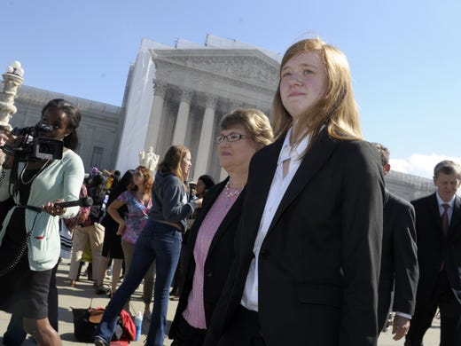 Abigail Fisher, right, who sued the University of Texas, walks outside the Supreme Court on Wednesday. The court is taking up a challenge to a University of Texas program that considers race in some college admissions.