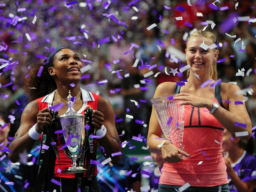Serena Williams, left, and Maria Sharapova, pose with their championship and runner-up trophies, respectively, following the singles final in Istanbul.