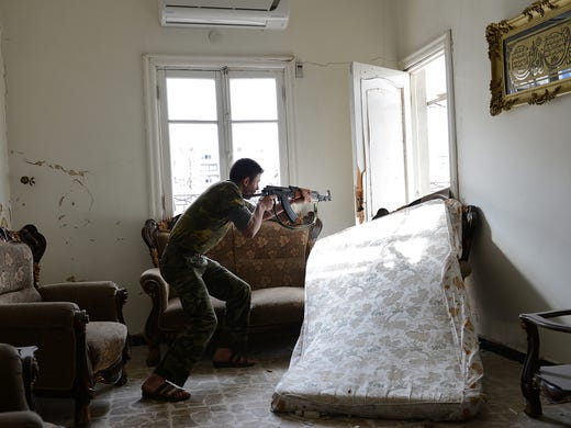 A rebel fires at Syrian government troops on Oct. 30 in the Salaheddin district in Aleppo.