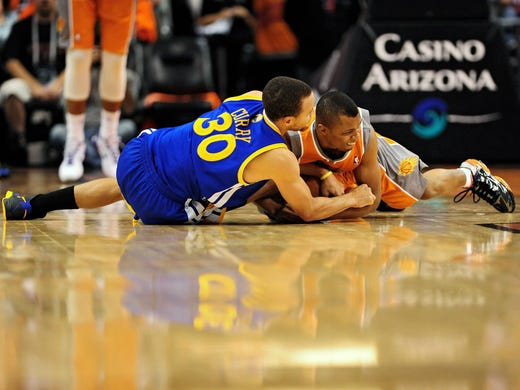 Warriors guard Stephen Curry, left, and Suns guard Sebastian Telfair hit the floor for a loose ball in Golden State's 87-85 win Wednesday. Flip through this gallery for more top shots from Day Two of the NBA season.