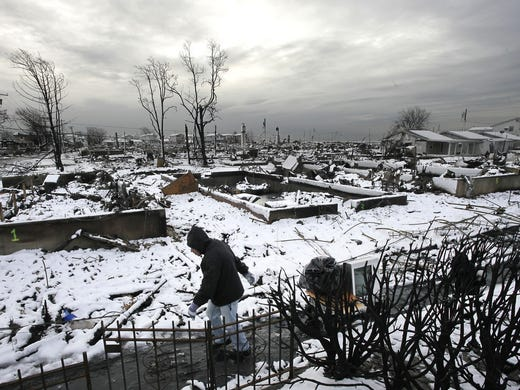 Damon Rasinya carts debris from his home past the fire-scorched landscape on Nov. 8 in Breezy Point, N.Y. A nor'easter storm disrupted recovery efforts from Hurricane Sandy and left a blanket of wet snow that downed power lines and snapped storm-weakened trees.