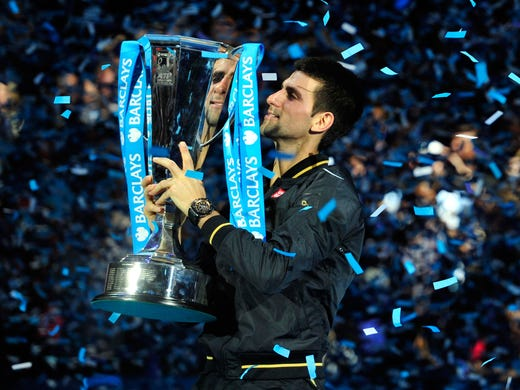 Novak Djokovic of Serbia hoists the championship trophy after defeating Roger Federer of Switzerland 7-6 (8-6), 7-5 on Monday in the ATP World Tour Finals in London.