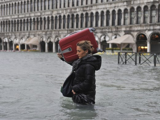 A tourist crosses St. Mark's Square in Venice, Italy, where high tides have flooded the city. Flooding is common this time of year.