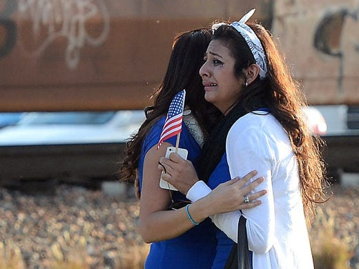 People cry after a trailer carrying wounded veterans in a parade was struck by a train on Nov. 15 in Midland, Texas. Four people were killed and 17 others injured when a parade float tried to get through a West Texas railroad crossing on its way to an honorary banquet.
