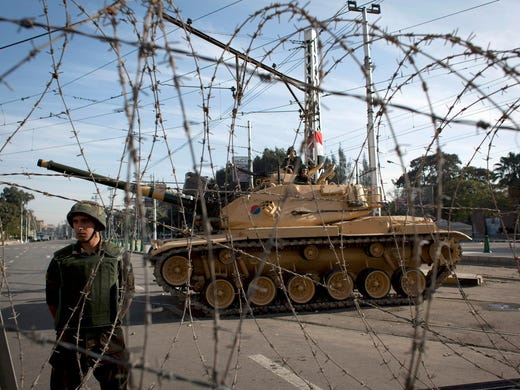 A soldier stands guard behind a barbed wire barrier protecting the presidential palace from protesters on Dec. 6 in Cairo.