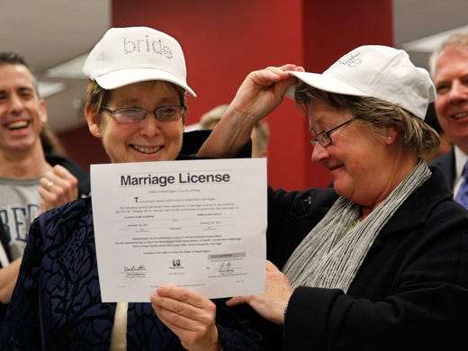 Claudia Gorbman, left, and partner Pam Keeley display their marriage license on Dec. 6 in Seattle. Dozens of same-sex couples obtained their marriage licenses in Washington state, hours after Gov. Chris Gregoire signed a voter-approved law legalizing gay marriage.