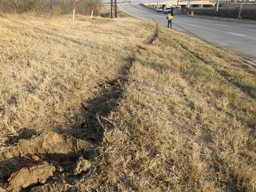 Tire ruts are seen on the ground with skid marks, at rear on road, at the site of single vehicle accident involving Dallas Cowboys player Josh Brent as a news cameraman, rear, films the area in Irving, Texas. Brent is facing an intoxication manslaughter charge after a one-vehicle accident that killed linebacker Jerry Brown, a member of the team's practice squad.