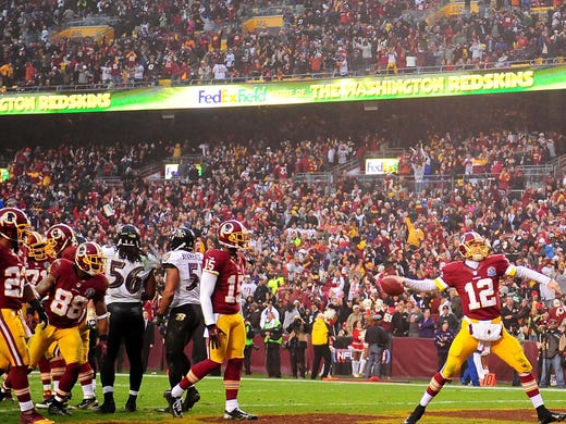 Washington Redskins quarterback Kirk Cousins (12) spikes the ball after tying the game with a two point conversion against the Baltimore Ravens at FedEx Field. The Redskins won 31-28 in overtime.