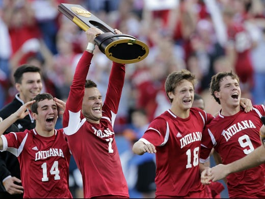 Indiana's Harrison Petts (7) and teammates T.J. Popolizio (14), Richard Ballard (18) and Andrew Oliver (9) rush the field with the championship trophy after winning the NCAA Division I College Cup.