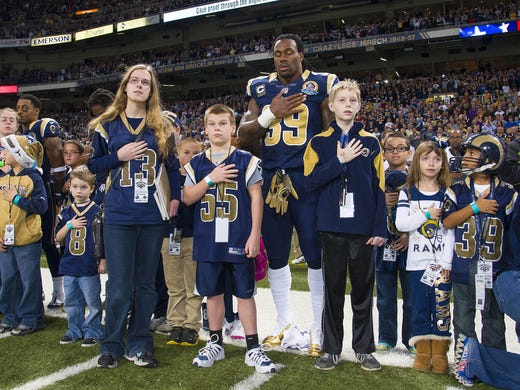 St. Louis Rams running back Steven Jackson (39) stands with children for a moment of silence for the victims in the Newtown, Conn. school shooting before the game against the Minnesota Vikings at the Edward Jones Dome.