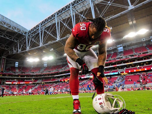 Arizona Cardinals defensive end Darnell Dockett (90) takes off his gloves after the game against the Detroit Lions at University of Phoenix Stadium.  The Cardinals beat the Lions 38-10.