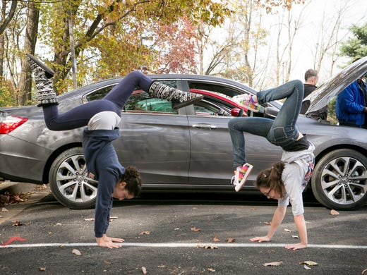 Cecilia Girvin and friend Jessie Goldenberg, both gymnasts, practice their handstands in front of the 2013 Honda Accord, winner of the Midsize Sedan Showdown asCecilia's dad, Patrick takes a closer look at the cars.