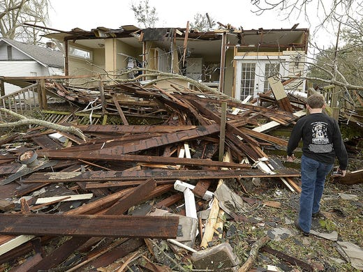 Mitchell Fordham walks through debris on his father's rental property on South Carlen Street on Dec. 26 in Mobile, Ala. A Christmas Day tornado caused extensive damage to homes, a school and a church.