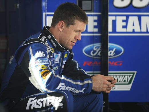 Carl Edwards checks his smart phone in the garage area during Sprint Cup Series Preseason Thunder testing at Daytona International Speedway on Jan. 12, in Daytona Beach, Fla.