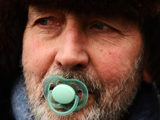 "A man with a pacifier joins thousands of Russians at a protest Jan. 13 in Moscow against a new law that bans U.S. adoptions of Russian orphans. The ""March Against the Scum"" was aimed at naming and shaming lawmakers who fast-tracked the anti-adoption legislation."