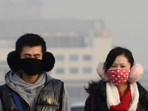 A couple wear face masks to protect themselves from air pollution on Jan. 15 in Beijing. At its highest level, the particle pollution index was above 700 micrograms per cubic meter but has gradually declined to 350 micrograms. The World Health Organization considers 25 micrograms a safe level.