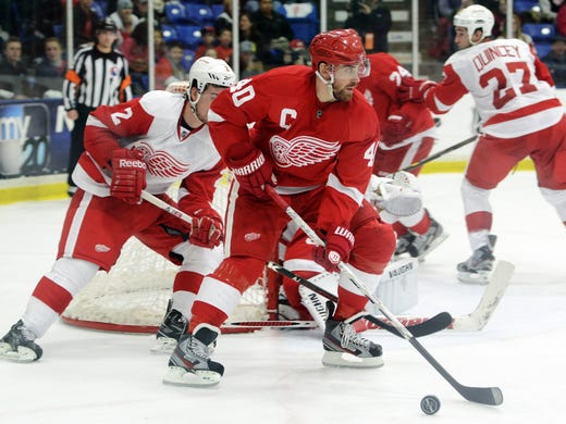 Detroit Red Wings captain Henrik Zetterberg uses his body to keep the puck away from  Brendan Smith during the second period of their Red and White scrimmage at Compuware Arena in Plymouth, Mich.