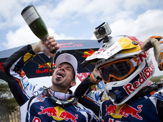 <strong>Stage 14:</strong> France's Cyril Despres, left, celebrates his fifth Dakar Rally motorbike title with a bottle of champagne next to his teammate and second-place finisher Ruben Faria of Portugal after the final stage, Saturday in Santiago, Chile.