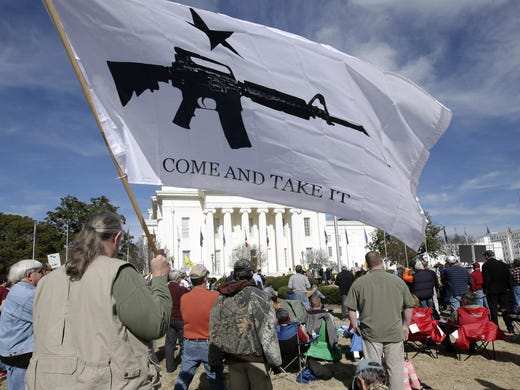 "James Wilson carries a ""Come and take it"" flag Saturday during a gun rights demonstration on the lawn of the Capitol in Montgomery, Ala."