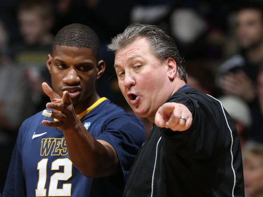 West Virginia Mountaineers coach Bob Huggins talks to guard Aaron Brown (12) during a game against the Purdue Boilermakers at Mackey Arena.