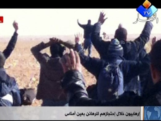 """In this image made from video, a group of people believed to be hostages kneel in the sand with their hands in the air at an unknown location in Algeria. An Algerian security official says de-mining squads searching for explosives found """"numerous"""" bodies on Jan. 20 at a gas refinery where Islamic militants took dozens of foreign workers hostage."""